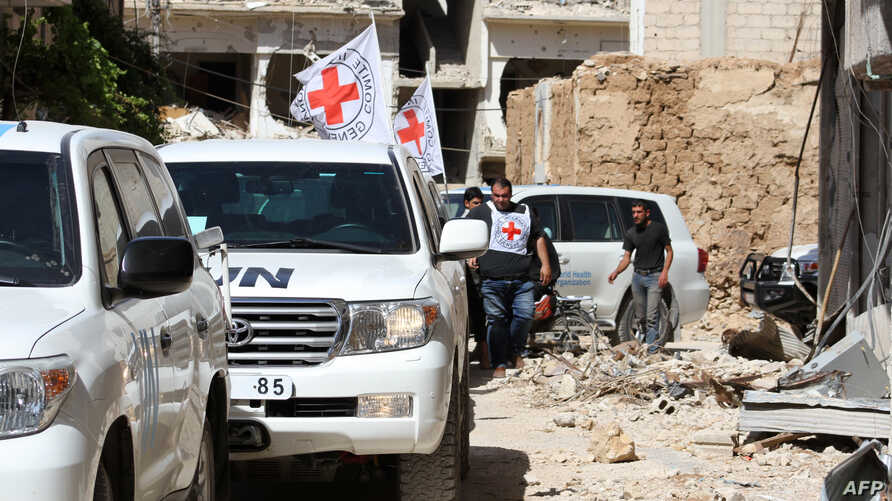Vehicles of the International Committee of the Red Cross (ICRC) and the United Nations wait on a street after an aid convoy entered the rebel-held Syrian town of Daraya, southwest of the capital Damascus, on June 1, 2016.