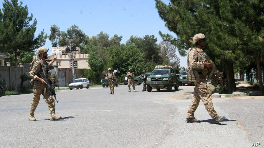 FILE - Afghanistan, security forces take position during a fighting outside a government compound  in the city of Lashkar Gah, capital of Helmand province, Afghanistan, May. 13, 2015.
