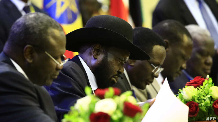 President of South Sudan, Salva Kiir signs a final power-sharing deal between South Sudanese arch-foes, Aug. 5, 2018, in Khartoum.