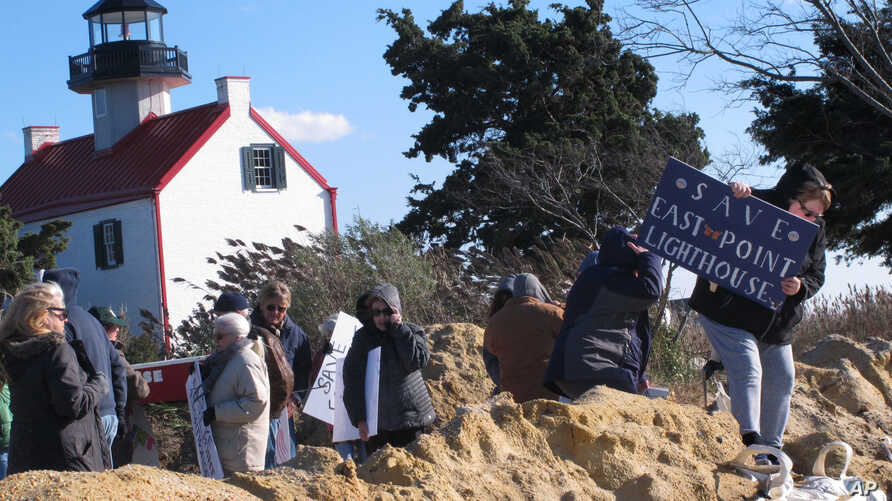 """Volunteers hold a """"Save The Lighthouse"""" rally near the East Point Lighthouse in Maurice River Township, N.J., Nov. 10, 2018."""