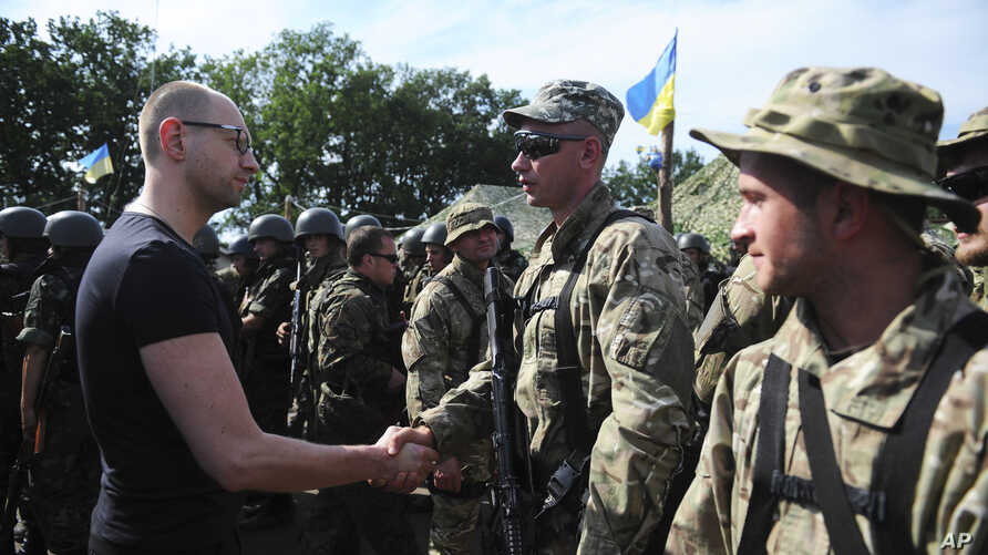 Ukrainian Prime Minister Arseniy Yatsenyuk (l) greets a soldier during inspection of a Ukrainian Army position outside the eastern town of Slovyansk, July 16, 2014.