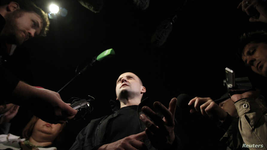Opposition leader Sergei Udaltsov (C) talks to the media after leaving a building of the Russian Investigative Committee in Moscow, October 17, 2012. Russian investigators have begun criminal proceedings against the prominent leader of protests again