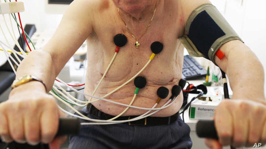 FILE - A man sits on an ergometer during an electrocardiogram in a doctor's surgical office.