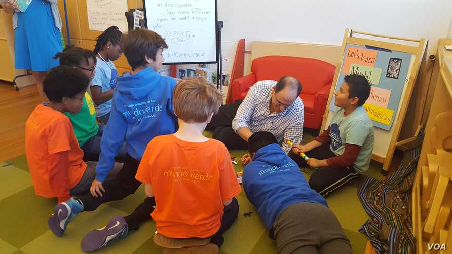 Students at Mundo Verde bi-lingual school work on solving a mystery with teacher David Levin.