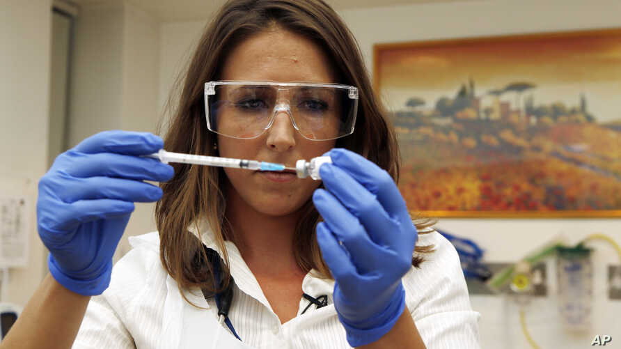 Dr. Felicity Hartnell, who is a clinical research fellow at Oxford University, holds a vial of an experimental vaccine against Ebola in Oxford, England, Sept. 17, 2014.