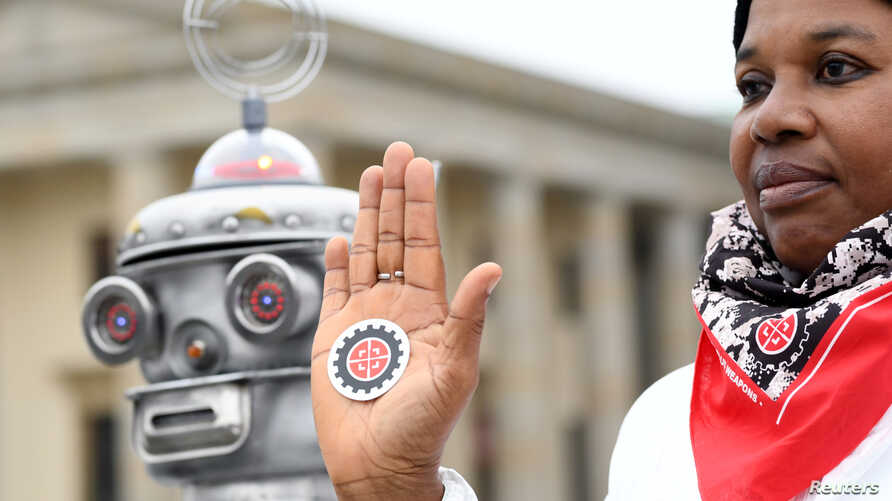 FILE - An activist from the Campaign to Stop Killer Robots, a coalition of non-governmental organizations opposing lethal autonomous weapons or so-called 'killer robots', protests at Brandenburg Gate in Berlin, Germany, March, 21, 2019.
