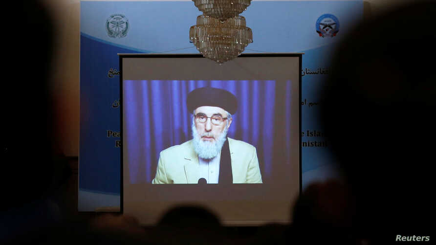 FILE - A screen shows the broadcast of Gulbuddin Hekmatyar during a signing ceremony with Afghan government at the presidential palace in Kabul, Afghanistan, Sept. 29, 2016.