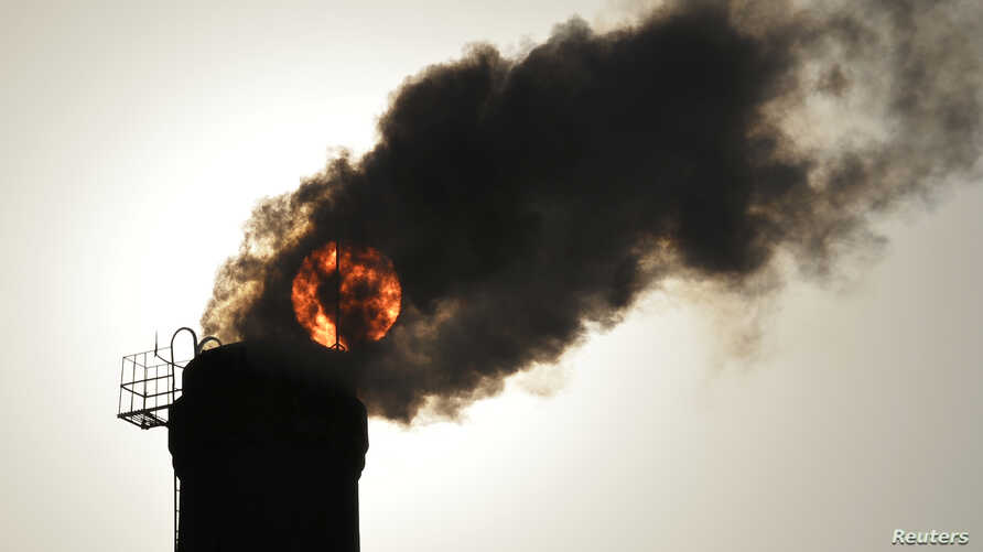 The sun is seen behind smoke billowing from a chimney of a heating plant in Taiyuan, Shanxi province December 9, 2013.