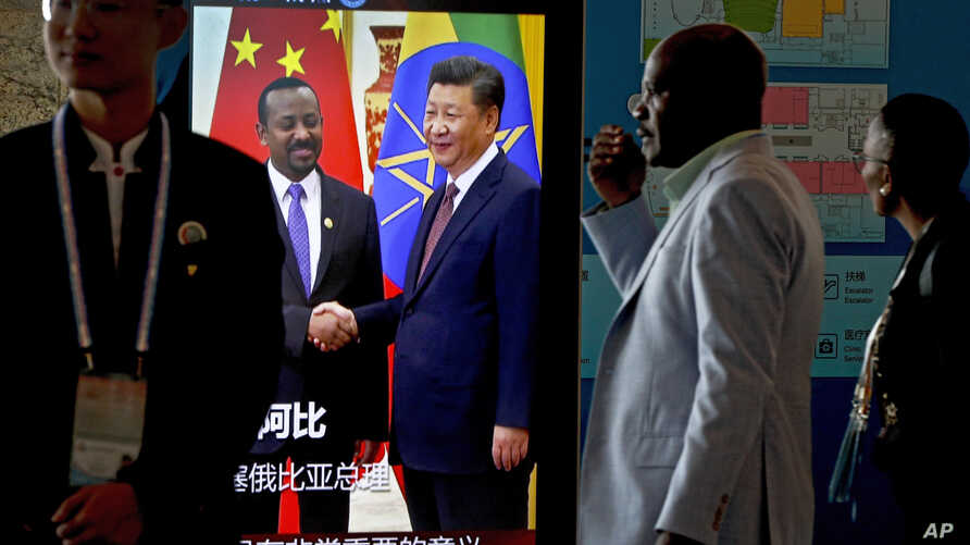African delegates walk by a screen panel showing a footage of Chinese President Xi Jinping with Ethiopia's Prime Minister Abiy Ahmed ahead of the Forum on China-Africa Cooperation in Beijing, Sept. 3, 2018.