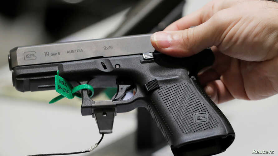 A man holds a Glock handgun during the annual National Rifle Association convention in Dallas, Texas, May 6, 2018.