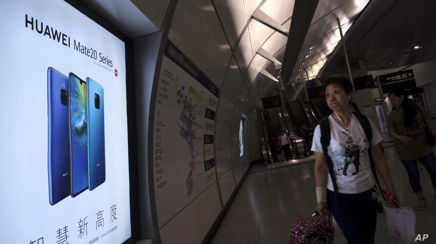FILE - A woman walks past an advertisement for Huawei at a subway station in Hong Kong, Dec. 5, 2018.