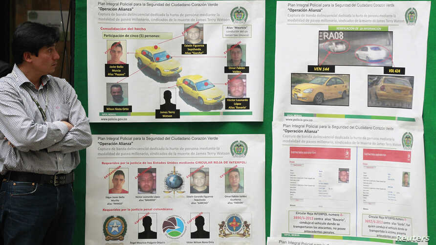 """FILE - A journalist looks at posters detailing the arrest operation of a suspect in the death of U.S. Drug Enforcement Administration Special Agent James """"Terry"""" Watson, in Bogota."""