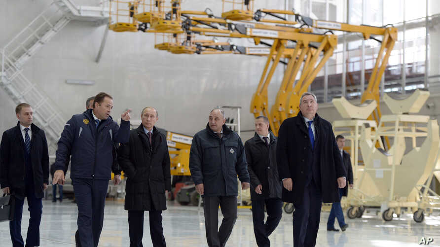 Russian President Vladimir Putin, third left, escorted by Russian Federal Space Agency head Igor Komarov, second left, walks through a working hall while visiting the Vostochny Cosmodrome near Uglegorsk, the city in eastern Siberia in the Amur region