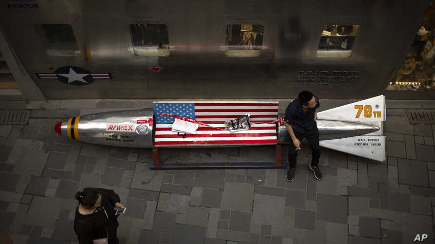 In this Thursday, July 5, 2018, photo, a man sits on a promotional gimmick in the form of a bomb and the U.S. flag outside a U.S. apparel shop at a shopping mall in Beijing.