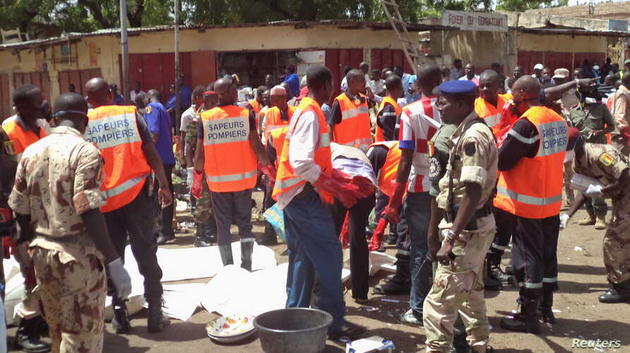 First responders gather at the site of a suicide bombing in N'djamena, Chad, where a man dressed in a woman's burqa blew himself up in the main market, killing 15 people and injuring 80, July 11, 2015.