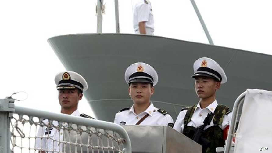 Chinese naval personnel stand at attention on the deck of the People's Liberation Army Navy's guided missile frigate FFG Zhoushan (file photo)