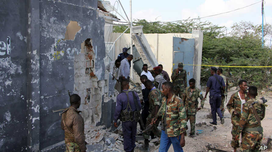 Somali soldiers stand near a destroyed building after a suicide attack that targeted a convoy escorting a senior military general in Mogadishu, Sept, 18, 2016.