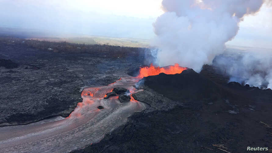 FILE - A cinder-and-spatter cone is building at fissure 8 as the cone continues to feed a lava flow that reaches the ocean at Kapoho during ongoing eruptions of the Kilauea Volcano in Hawaii, June 11, 2018. Next week, a major hurricane could brush by