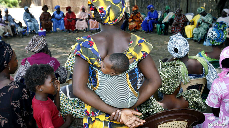FILE - A mother carrying an infant on her back attends a meeting of women from several communities eradicating female genital mutilation, in Diabougo, Senegal.