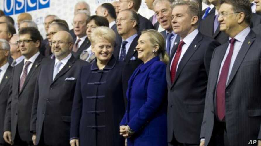 US Secretary of State Hillary Rodham Clinton, center, is flanked by Lithuania's FM Audronius Azubalis, right, and Lithuania's President Dalia Grybauskaite, left, as they attend an international conference of the Organization for Security and Cooperat