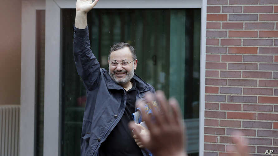 Ahmed Mansour waves as he leaves the security checkpoint of the Moabit jail in Berlin, Germany, June 22, 2015.