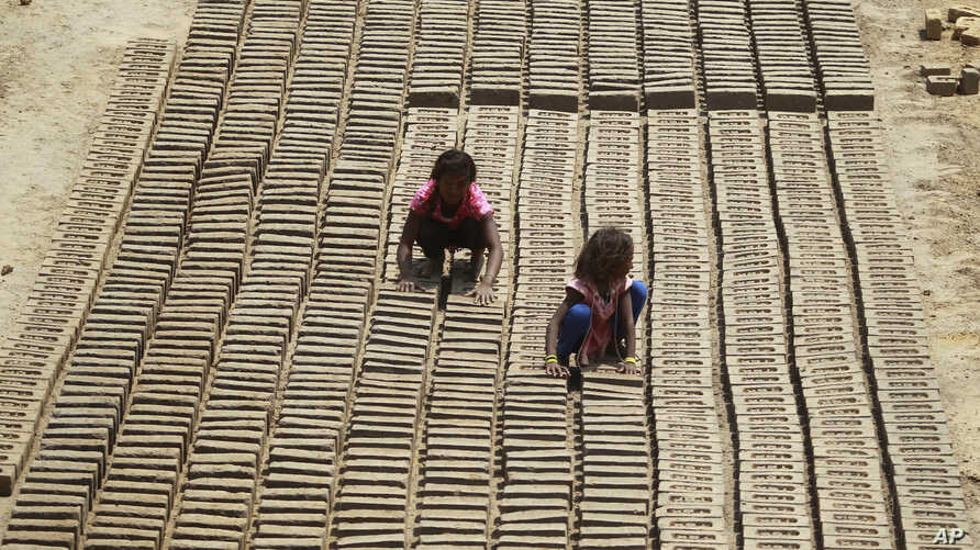 Indian children work at a brick factory on the outskirts of Jammu, May 1, 2018.