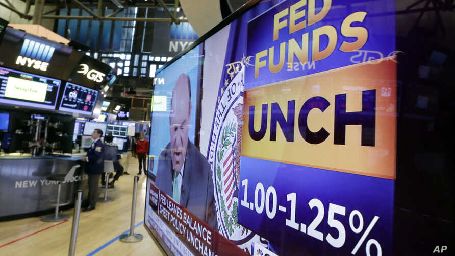 A television screen on the floor of the New York Stock Exchange shows the rate decision of the Federal Reserve, July 26, 2017. The Federal Reserve is keeping its benchmark interest rate unchanged at a time of low inflation, which remains persistently