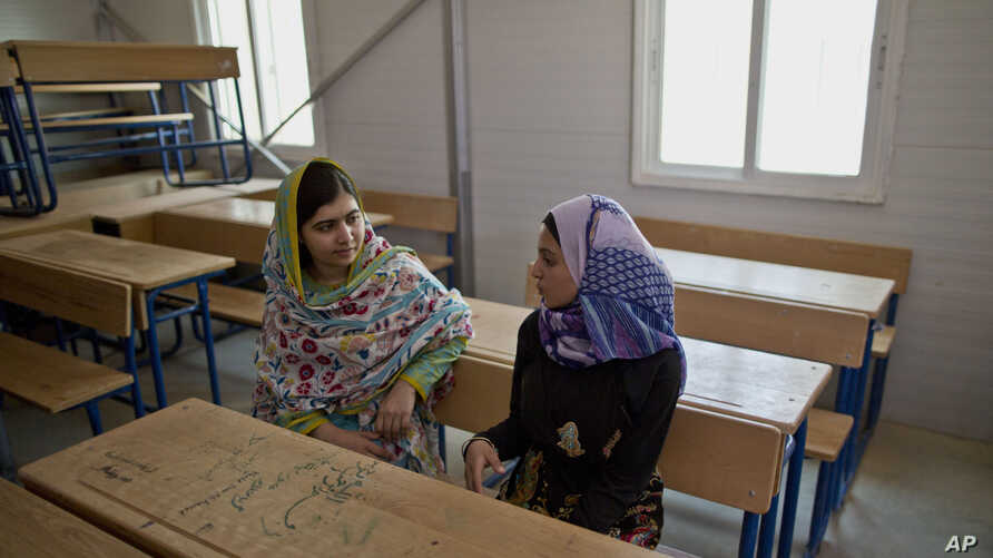 Nobel Peace Prize laureate Malala Yousafzai, 18, left, and Mezon al-Melihan, a 17-year-old refugee from the southern Syrian town of Deraa, talk while visiting a class at Azraq refugee camp, Jordan, July 13, 2015.