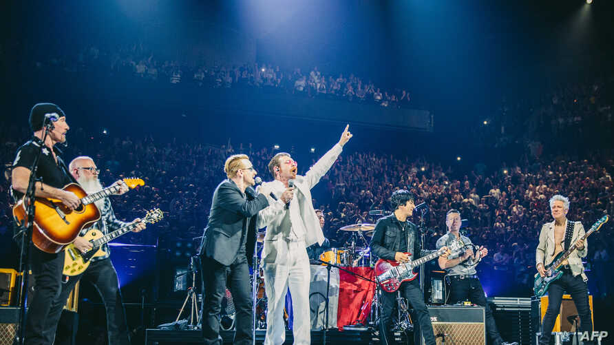 U2 frontman Bono, third from left, and Jesse Hughes, fourth from left, of the Eagles of Death Metal perform with their bands at the packed 16,000-seat AccorHotels Arena in Paris, Dec. 7, 2015.