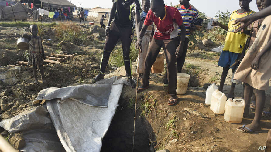 Displaced people draw water from a hole dug in the ground, in the United Nations camp for displaced people in the capital Juba, South Sudan, Jan. 19, 2016.