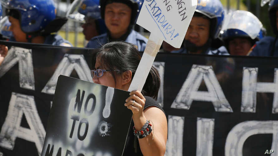 A protester displays her message during a rally at the Heroes Cemetery to protest the interment on its grounds last year of late Philippine dictator Ferdinand Marcos, as the nation marks the 31st anniversary of the People Power revolution that ended