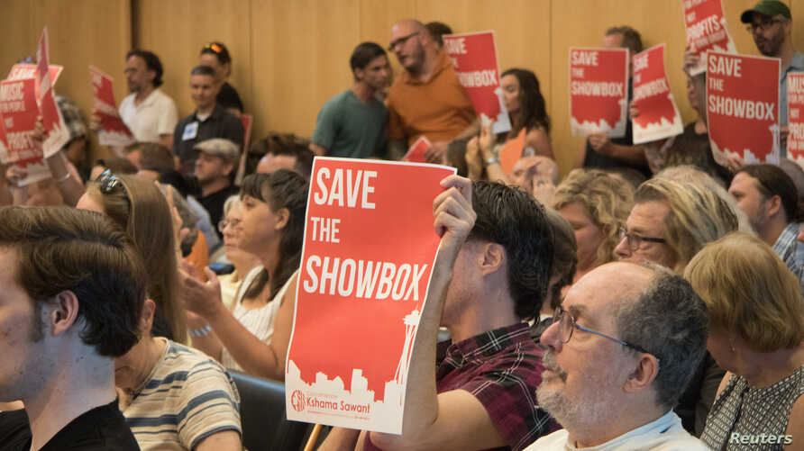 Supporters of music venue The Showbox wave signs at a Seattle City Council meeting, Aug. 6, 2018.