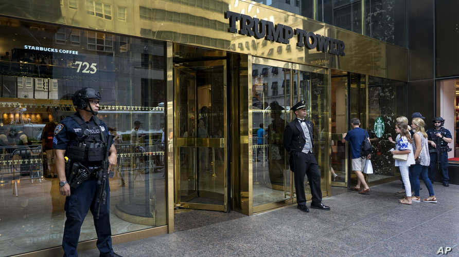 FILE - People pass police security an a building doorman in front of Trump Tower in New York.