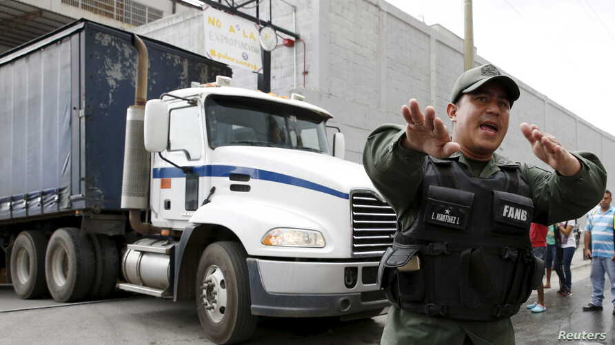 A Venezuelan National Guard walks in front of a truck as it leaves the facility used by Empresas Polar as a distribution center, while company employees shout inside, during the occupation of its installations by government representatives in Caracas