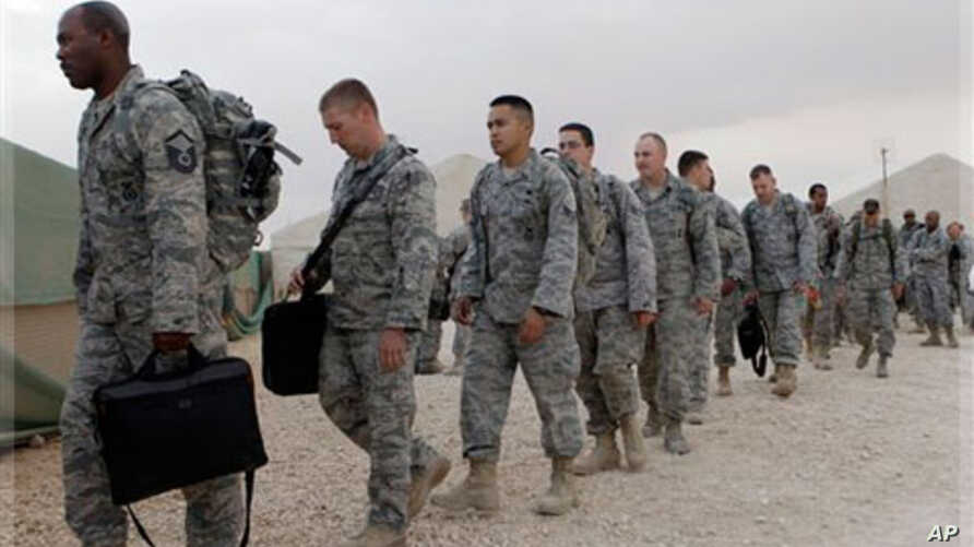 U.S. servicemen line up to board a bus as they begin their journey home at al-Asad Air Base west of Baghdad, Iraq, Tuesday, Nov. 1 , 2011.