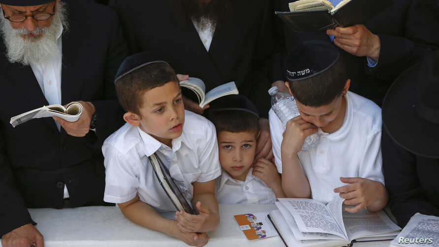 Visitors pray at the gravesite of the 'Lubavitcher Rebbe,' Rabbi Menachem Mendel Schneerson, at the Old Montefiore Cemetery in the Queens borough of New York June 30, 2014.