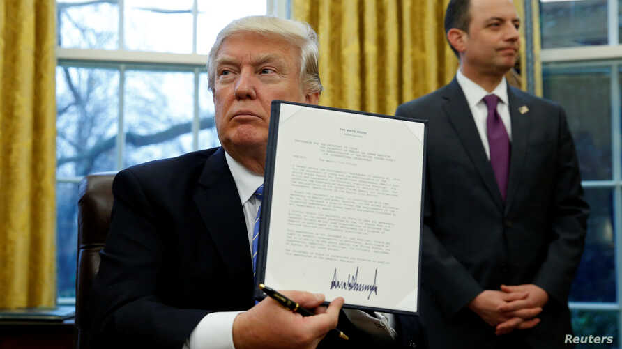 U.S. President Donald Trump holds up the executive order on the reinstatement of the Mexico City Policy after signing in the Oval Office of the White House in Washington, Jan. 23, 2017.