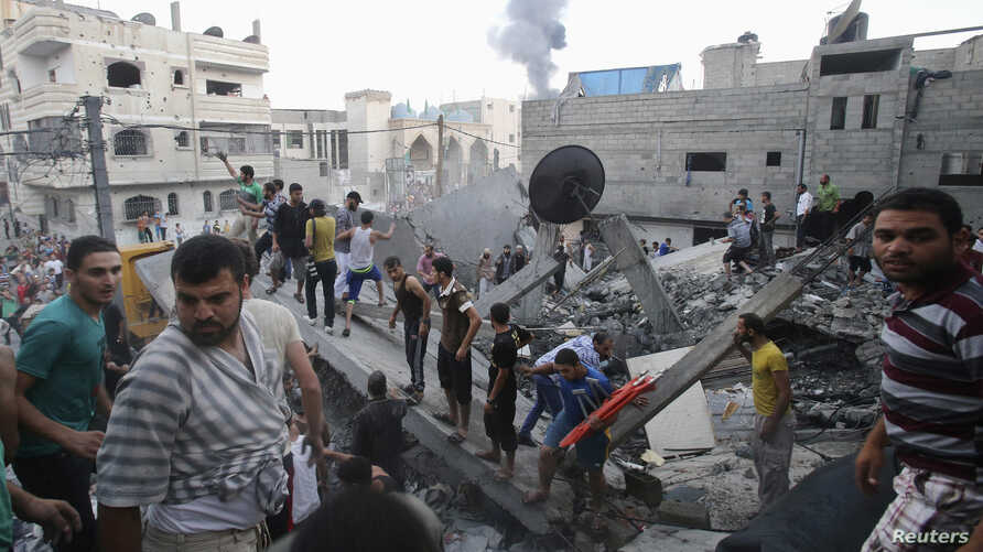 Smoke rises from buildings following what witnesses said was an Israeli air strike, as Palestinians search for victims under the rubble of a house that police said was destroyed in another Israeli air strike in Rafah in the southern Gaza Strip, July ...
