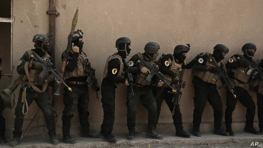 FILE - Soldiers from the 1st Battalion of the Iraqi Special Operations Forces are stacked against a building during a training exercise to prepare for the operation to retake Mosul from Islamic State militants, in Baghdad, Iraq, Aug. 13, 2016.