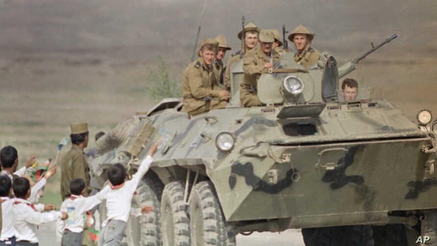 Afghan children and a soldier bid farewell to Soviet soldiers riding atop an armored personnel carrier as the official troop withdrawal begins after nearly a decade long military intervention in war-torn Afghanistan, Sunday, May 15, 1988, Kabul, Afgh