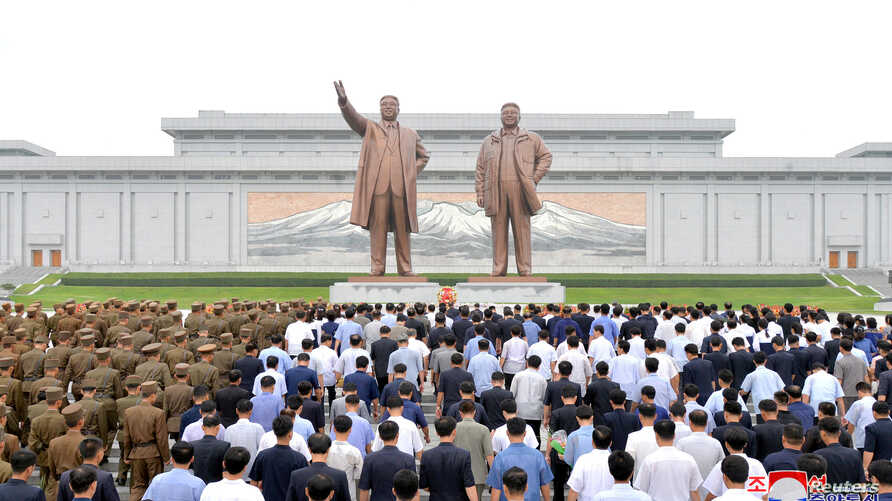 FILE - People and soldiers gather to offer flowers to the statues of state founder Kim Il Sung and former leader Kim Jong Il on the Day of Songun at Mansu hill, Pyongyang, North Korea, in this undated photo released by North Korea's Korean Central Ne