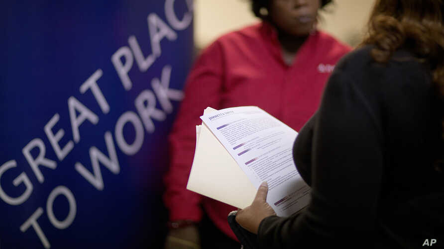 FILE - Jimmetta Smith of Lithonia, Ga., right, holds her resume while talking with Rhonda Knight, a senior recruiter for Delta airlines, at a job fair in Marietta, Ga., Nov. 14, 2013.