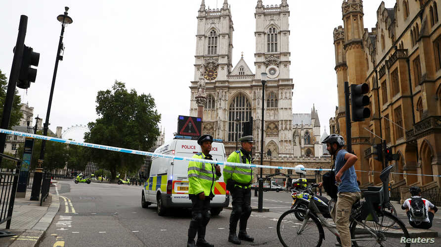 Police officers stand at a cordon after a car crashed outside the Houses of Parliament in Westminster, London, Britain, Aug. 14, 2018.