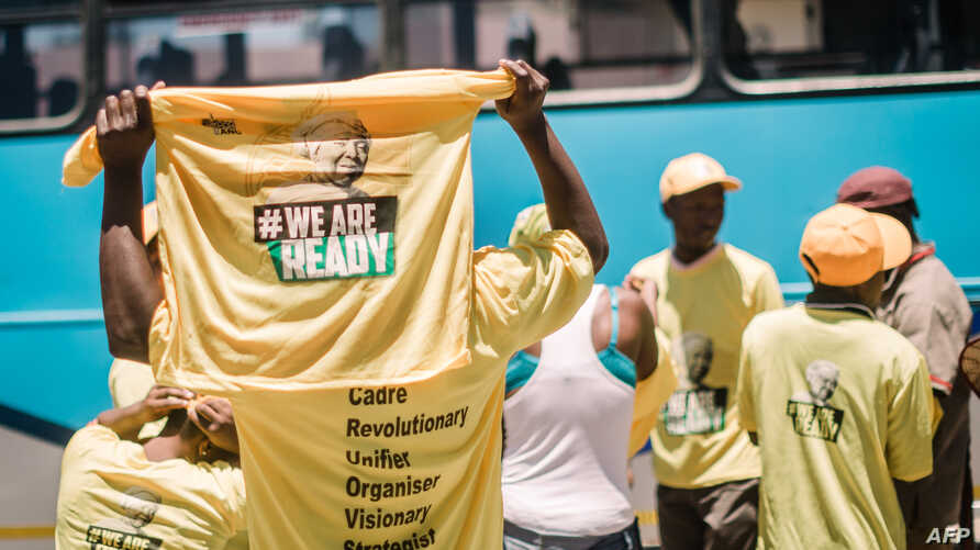 FILE - Supporters of candidate for South Africa's ruling African National Congress (ANC) party leadership Nkosazana Dlamini-Zuma hold T-shirts as they arrive to hear her speak during her final campaign at a rally in Clermont township south of Durban,