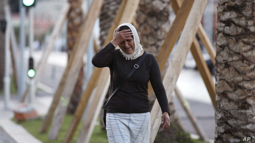 A woman cries asking for her son as she walk near the scene of an attack after a truck drove onto the sidewalk and plowed through a crowd of revelers who'd gathered to watch the fireworks in the French resort city of Nice, southern France, Friday, Ju