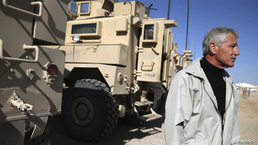 FILE - U.S. Secretary of Defense Chuck Hagel stands next to MRAP vehicles after speaking to U.S. troops at Camp Bastion, Afghanistan, Dec. 8, 2013.