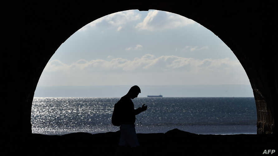 FILE - A man walks along the sea front in Swansea on October 13, 2015.