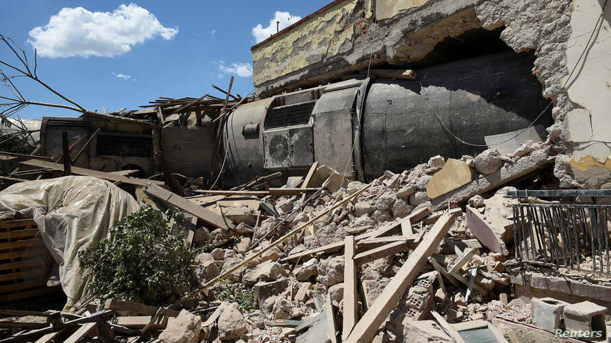A train carriage is seen after crashing into a house following a derailment, in the town of Adendro in northern Greece, May 14, 2017.