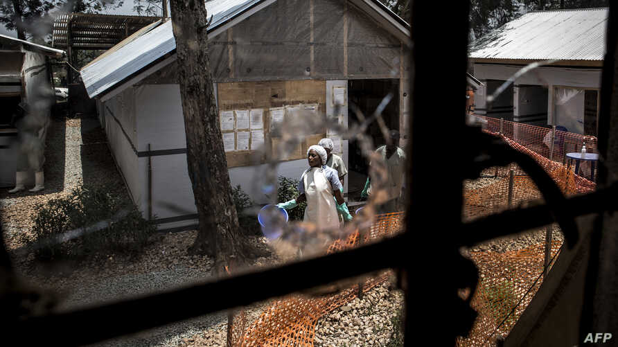 Health workers are seen through a bullet hole left in the window of an Ebola treatment center, which was attacked in early on March 9, 2019, in Butembo, Democratic Republic of the Congo.
