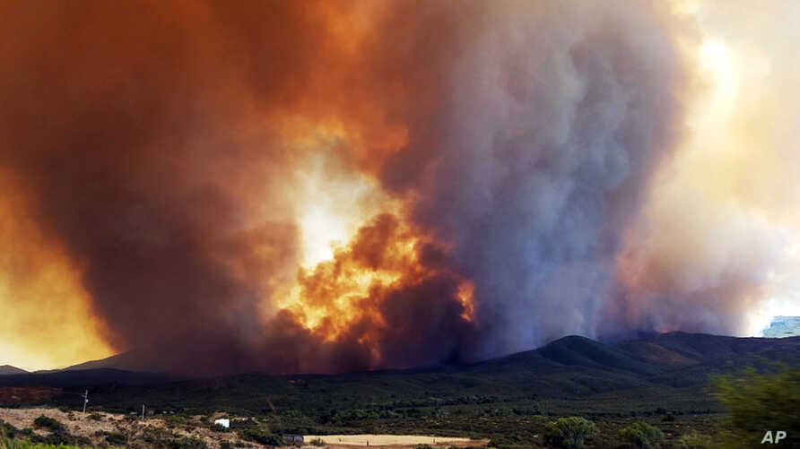 In this frame from video, flames and smoke can be seen rising from a fire near Mayer, Arizona, June 27, 2017.